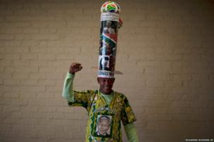 A mourner poses with his homemade hat