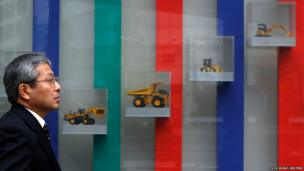 A man walks in front of a display window showing models of heavy machinery