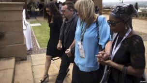 Bono and his wife Ali Hewson (L) walk with Zelda La Grange (2nd R), former assistant to Nelson Mandela, after viewing the coffin in Pretoria, 11 December