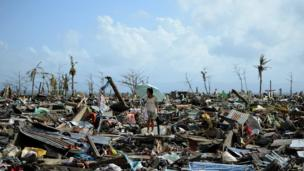 A survivor walks among the debris of houses destroyed by Super Typhoon Haiyan in Tacloban in the eastern Philippine island of Leyte on 11 November 2013