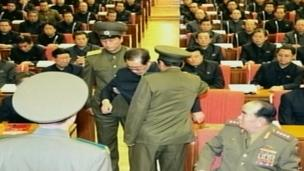 This undated image grab taken from footage shown by North Korea's KCTV and released by South Korea's Yonhap news agency on 9 December 2013 shows Chang Song-thaek (C) reportedly being dragged out from his chair by two police officials during a meeting in Pyongyang