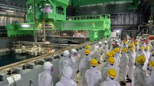 This picture taken on 26 November 2013 shows the operation to move a spent fuel rod to a cask in the spent fuel pool of the unit four reactor building, as Tepco transfers the fuel rods from the crippled No. 4 reactor building to another fuel pool at Tepco's Fukushima Daiichi nuclear plant at Okuma town in Fukushima prefecture