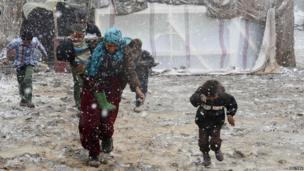 Syrian refugees run for cover from snow during a winter storm in Zahle town, in the Bekaa Valley December 11, 2013