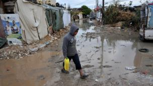 A Syrian refugee boy walks in a muddy alley at a makeshift camp in the village of Kfarkahel, in the Kura district near the northern city of Tripoli, on December 11, 2013