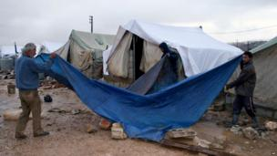 Syrian refugees cover their tent with a tarp as a heavy snowstorm batters the region, in a camp for Syrians who fled their country's civil war, in the Bekaa valley, eastern Lebanon, Wednesday, Dec. 11, 2013