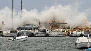 A car drives in front of waves crashing against the rocks in the northern Lebanese port city of Tripoli
