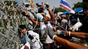 Anti-government protesters remove barbed wire before a small group of them briefly entered the compound of the prime minister's office, known as the Government House, in Bangkok