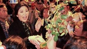 Thai Prime Minister Yingluck Shinawatra (L) receives flowers from her supporters as she arrives at the airport in Chiang Mai province. 11 December 2013