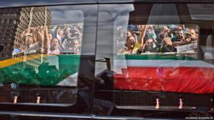 South African mourners, wave and shout as the hearse carrying the body of former South African President Nelson Mandela passes by, in Pretoria, South Africa,