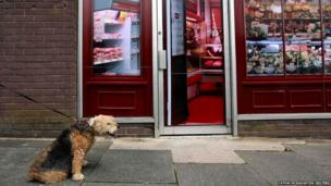 A man walks his dog past a vacant shop, with graphics pasted to the outside to make it look like a working butcher's shop, in the village of Belcoo, Northern Ireland, 3 June 2013