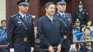 Ousted Chinese politician Bo Xilai, centre, stands as the Shandong Provincial Higher People's Court announces the decision of the second trial of Bo, in Jinan, China's Shandong Province, 25 October 2013