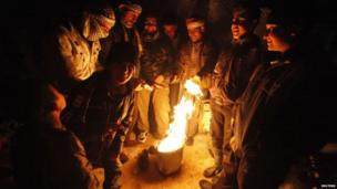 Syrian refugees from the town of Qara gather around a fire to keep themselves warm at a camp in the Lebanese border town of Arsal, in eastern Bekaa Valley.