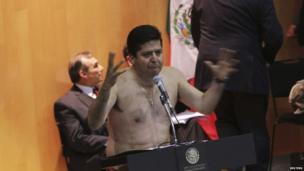Antonio Garcia of the Party of the Democratic Revolution addresses the Mexican Congress after stripping down to his underwear during the overnight debate on energy privatisation, to symbolize the stripping of Mexico's oil wealth in Mexico City, 12 December.