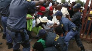 People are helped from the floor after South African police open a gate to a park and ride at the Tshwane Events Centre where buses shuttled well-wishers to a queue to view the body of Nelson Mandela, lying in state at the Union Buildings in Pretoria on 13 December.