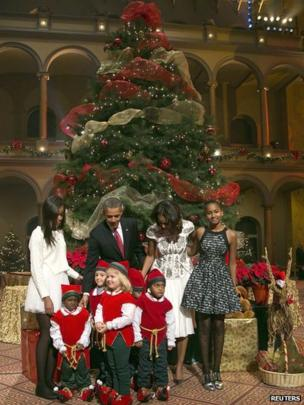 "U.S. President Barack Obama (2nd L), his wife Michelle (2nd R) and their daughters Malia (top L) and Sasha (top R) are greeted by a team of elves made up of former patients of the Children""s National Medical Center, as the Obamas arrive a taping of the Christmas in Washington television benefit program at the National Building Museum in Washington December 15, 2013."