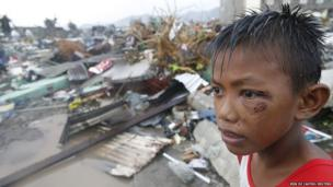 A boy who was wounded by flying debris due to Typhoon Haiyan stays at the ruins of his family's house in Tacloban city, 10 November 2013