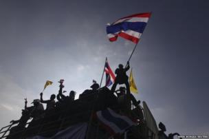 A protester waves a Thai national flag atop a truck at the Democracy Monument in central Bangkok, 4 November 2013