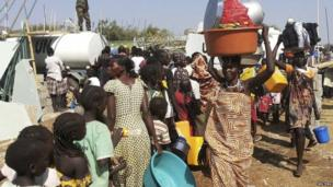 Civilians arrive to a shelter at the United Nations Mission in the Republic of South Sudan (UNMISS) compound on the outskirts of the capital Juba