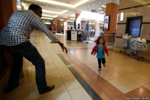 A child runs to safety as armed police hunt gunmen who went on a shooting spree at Westgate shopping centre in Nairobi, 21 September 2013