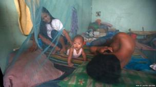 A family rests inside a mosquito net at an evacuation centre for typhoon survivors in Tacloban city