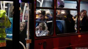 Injured people are taken away in a London bus following the collapse of a balcony at The Apollo Theatre