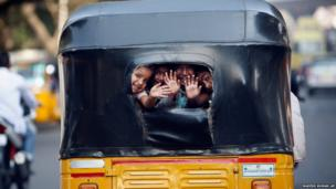 children wave at commuters as they look out from the back window of an auto rickshaw in Hyderabad, India