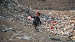 An Afghan child walks home at a refugee camp located on the outskirts of Kabul
