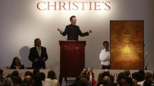 Christie's International Director, Asian Art, Hugo Weihe, center, acts as auctioneer for the painting of Indian artist Vasudeo S. Gaitonde during Christie's first auction in India in Mumbai, India, Thursday, Dec. 19, 2013.