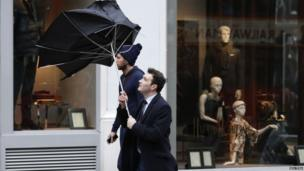 Pedestrians walk in wet and windy weather on Oxford Street in central London