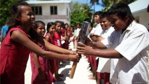 Student from Dai Nippon Primary School careful pass the baton in Tarawa, Kiribati