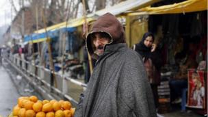 A Kashmiri street vendor, covered in woollen clothes, waits for customers in Srinagar, India, Monday, Dec. 23, 2013.