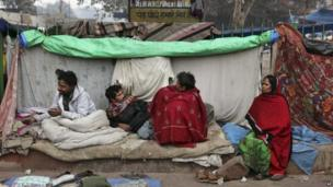 Indian homeless people sit wrapped in woollen clothes outside their makeshift shelter on a cold winter morning in New Delhi, India, Sunday, Dec. 22, 2013.