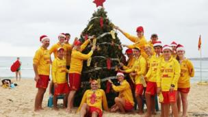Bondi lifeguards pose in front of their Christmas tree at Bondi Beach on 25 December 2013 in Sydney, Australia
