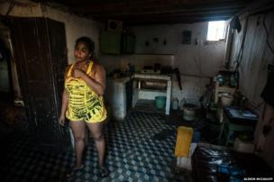 A young woman stands in her kitchen