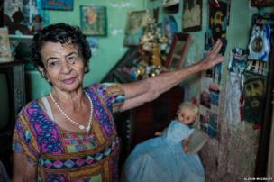 An elderly lady points towards a portrait of revolutionary, Camilo Cienfuegos