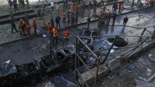 Firemen and onlookers gather around burnt cars at the scene of a huge blast that rocked central Beirut on December 27, 2013