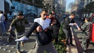 A Lebanese man carries an injured woman at the scene of an explosion in Beirut, Lebanon, (Dec. 27, 2013)