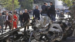 Onlookers and firemen gather around the remains of a vehicle that exploded in central Beirut (December 27, 2013)