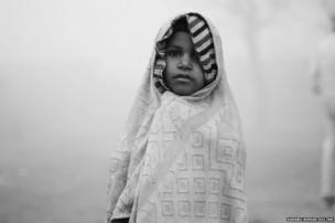 Ramza, a young girl, braves the bitter cold by wrapping herself in a towel.