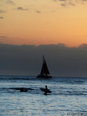 A man wades in the water at sunset in Honolulu, Hawaii