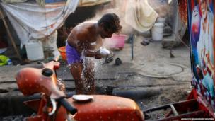 A migrant labourer bathes near the construction site of a hotel on a cold winter morning in Delhi