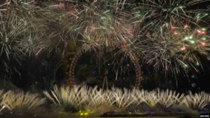 Fireworks explode around the London Eye wheel during New Year celebrations