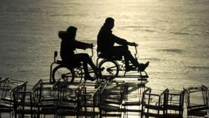 A couple ride ice bicycles on a frozen lake in Beijing on January 2, 2014