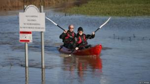 A woman and a man paddle a kayak on flooded land