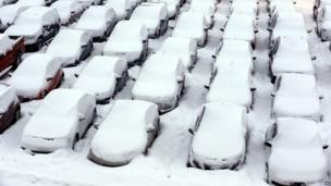 Cars are covered by snow in rental car parking lot at O'Hare International Airport in Chicago, Thursday, Jan. 2, 2014