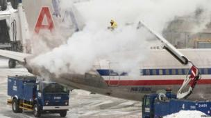 An American Airlines crew member sprays de-icing solution on a plane during a winter north eastern snow storm in Boston, Massachusetts January 2, 2014.
