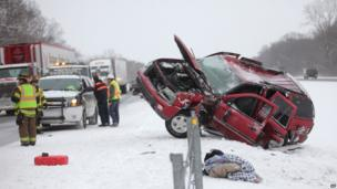 Emergency workers respond to a vehicle that slid off the road on Interstate 94 in Texas Township near Kalamazoo, Mich.