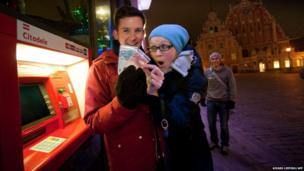 A couple displays euro banknotes after withdrawal from a cash machine in Riga, Latvia