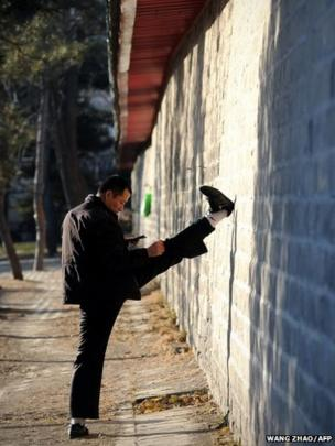 A man looks at his mobile phone as he exercises at a park in Beijing, China