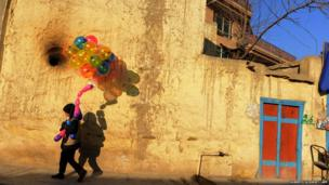 A young boy holds balloons in Kabul